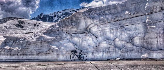 Rennrad vor Schneewand auf Gotthardpass